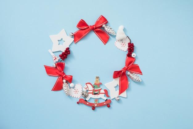 パステルブルーの背景に赤と白の装飾とクリスマスリース。新年のコンセプト。