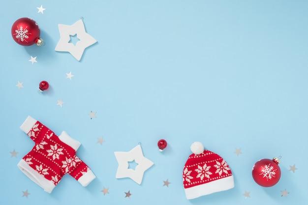 パステルブルーの背景に白と赤の装飾が施されたクリスマスまたは冬のフレーム。新年のコンセプト。