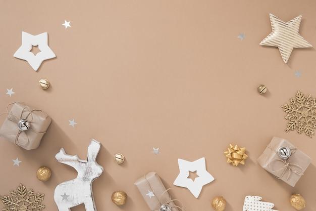 Рождественская композиция. рамка с подарками, ремесло и золотые украшения на пастельных бежевом фоне.