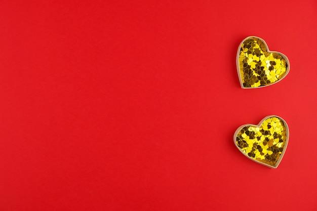 Два золотых сердца с конфетти на красной поверхности на день святого валентина. пространство для текста. веб-баннер или поздравительная открытка