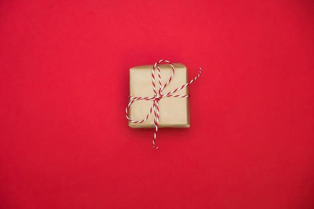 Подарочная коробка на красной поверхности на день святого валентина. пространство для текста. открытка или веб-баннер.