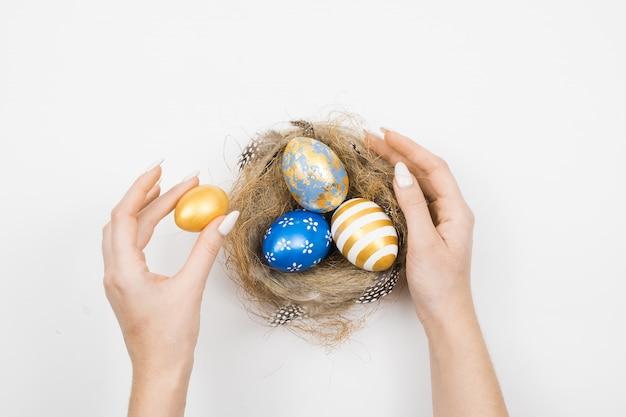 Украшенные пасхальные яйца золотые в гнезде при руки женщины изолированные на белой поверхности. минимальная концепция пасхи.