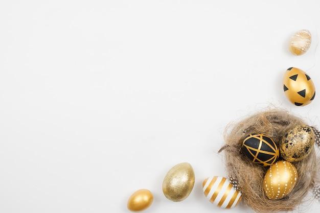黄金のイースターのフレームには、白い表面に分離された巣の卵が飾られています。最小限のイースターコンセプト。
