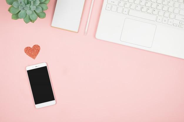 コピースペースとピンクの表面上のスマートフォン。レディースデスクトップ。平干し。上面図。バレンタインデーのモックアップテンプレート。