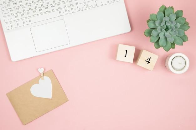 Композиция ко дню святого валентина февраль. нежная розовая поверхность, ноутбук и косметика. поздравительная открытка плоская планировка, вид сверху, копия пространства.