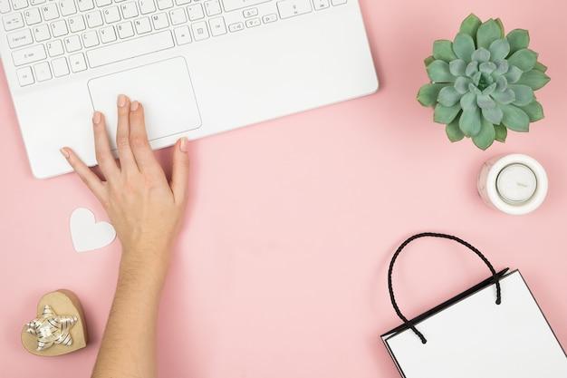 オンラインショッピングのコンセプト。ピンクの表面に携帯電話とラップトップを持つ女性の手。平面図、コピースペース。