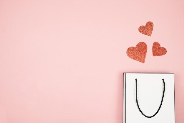 母の日セール、ピンクの表面に白いショッピングバッグのモックアップのバナー、チラシ、またはポスター。赤いハートで買い物をするための紙袋。バレンタイン・デー、