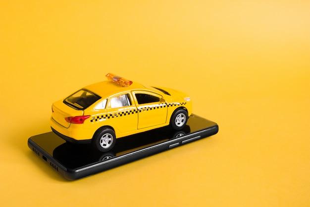 Городские такси мобильных онлайн концепции приложения. игрушка желтое такси модель автомобиля. рука смартфон с приложением службы такси на дисплее.