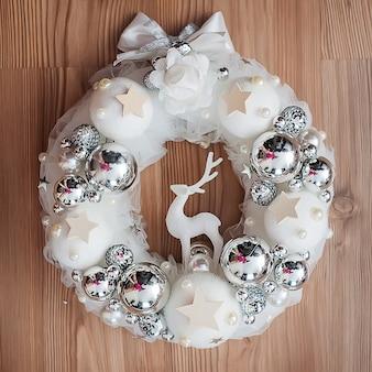 Белый рождественский венок с серебряными украшениями на деревянном фоне