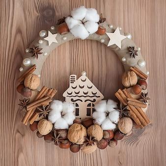 Натуральный рождественский венок с цинамоном, хлопком, орехами на фоне дерева