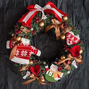 Рождественский венок с красными ягодами на черном фоне