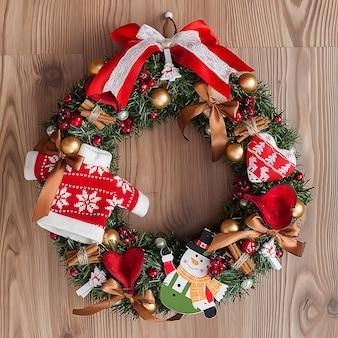 Рождественский венок с красными ягодами на деревянном фоне