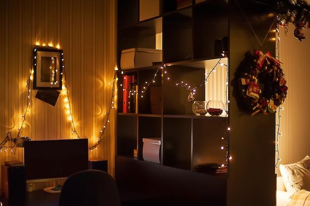 Рождественские украшения интерьера. гирлянды на стене, венок и рождественские огни