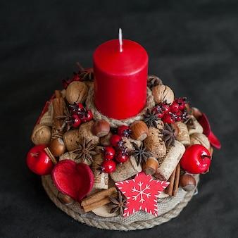 赤いクリスマスキャンドル、果実、シナモン、ナッツの装飾、黒の背景