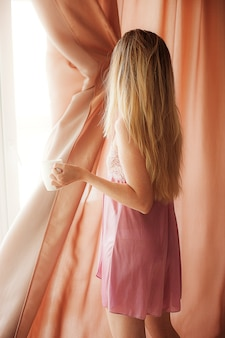 窓のカーテンを開いて幸せな女性のクローズアップ。素敵な女の子が目が覚めて前に立っている