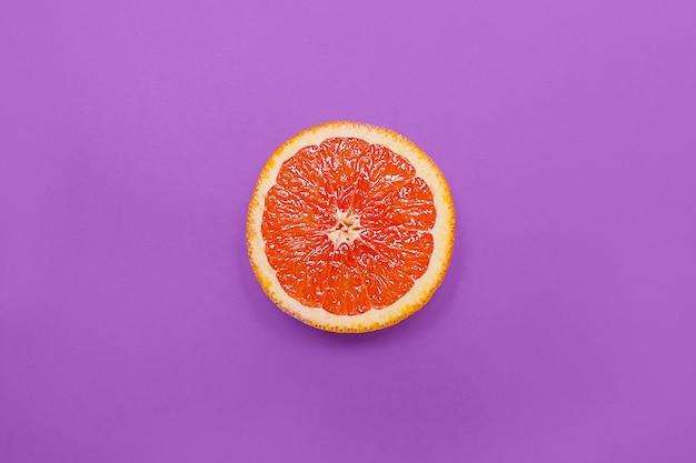 最小限のスタイル、創造的なレイアウトオレンジと紫色の背景にグレープフルーツ