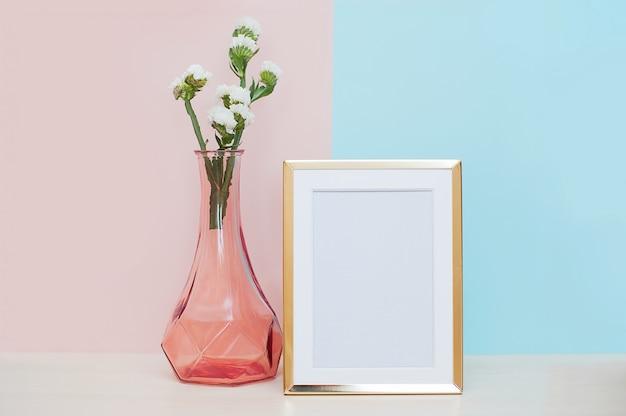 ゴールドブランクのフォトフレーム、花瓶、ピンクのブルーバックグラウンドの熱帯植物のあるモダンな家のインテリア