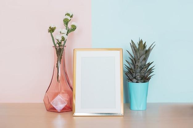 金のモダンな家のインテリアは、フォトフレーム、花瓶、ピンクのブルーのバックの熱帯植物