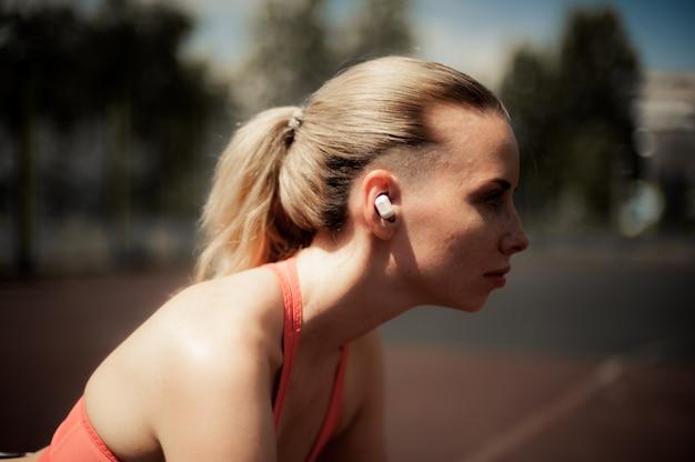 フィットネスの女性ワイヤレスヘッドフォンで音楽を聴く、ストリートで運動練習をする