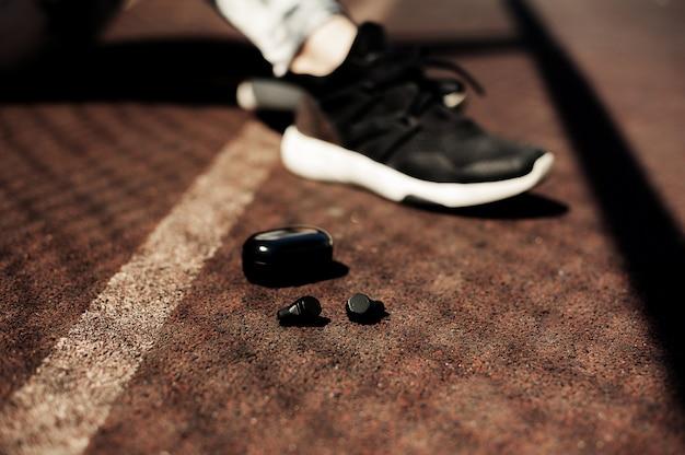 ランナーのための新しいスポーツ着用アクセサリー:ワイヤレスイヤホン、ランニングシューズ。イヤホン、彼