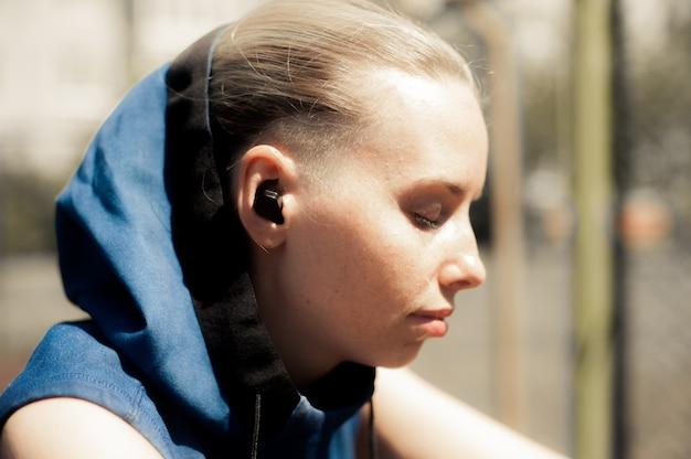 フィットネス女性ワイヤレスヘッドフォンで音楽を聴く。