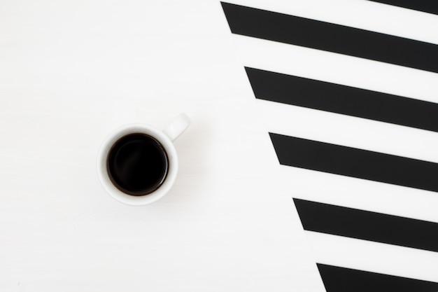ストライプの背景にコーヒーのカップとスタイリッシュな最小限の作業スペース