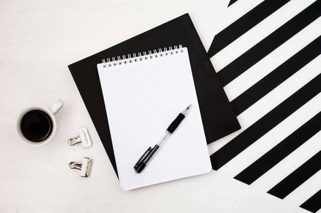 ノートパソコンのモックアップ、鉛筆、コーヒーの入ったスタイリッシュなミニマルワークスペース