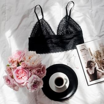 フラットレイ。トップビューブラックレースランジェリー、バラとピジョンの花束、ホワイトベッドのバのコーヒー