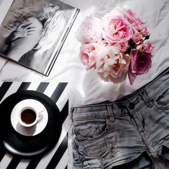 ショートパンツ、バラのブーケ、コーヒー、雑誌のフラットレイ