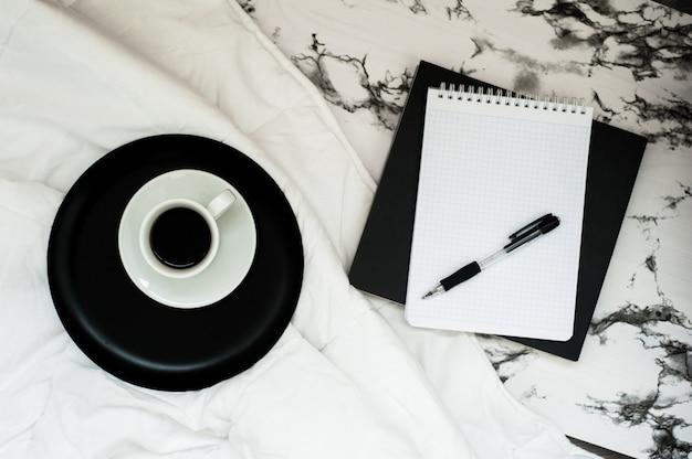 スタイリッシュな大理石の背景にコピースペースを持つノートブック、コーヒーカップと最小限の作業スペース