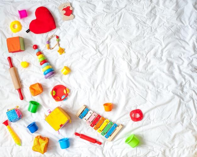 子供たちは、白い背景に明るいカラフルなおもちゃのフレーム。上面図。フラットレイ。テのためのスペースをコピーする