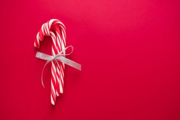 クリスマスと新年のグリーティングカードの赤い背景に銀の弓のキャンディー杖