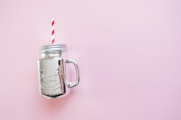 ピンクの背景にストローと銀製のクリスマスメーソンの瓶。冬のクリスマスフラットレイ