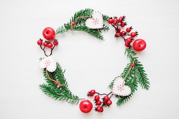 クリスマスの組成。クリスマスギフト、松枝、おもちゃで作られたフレームの花輪