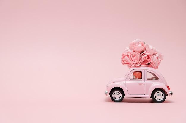 Розовый ретро игрушечный автомобиль с доставкой букета цветов