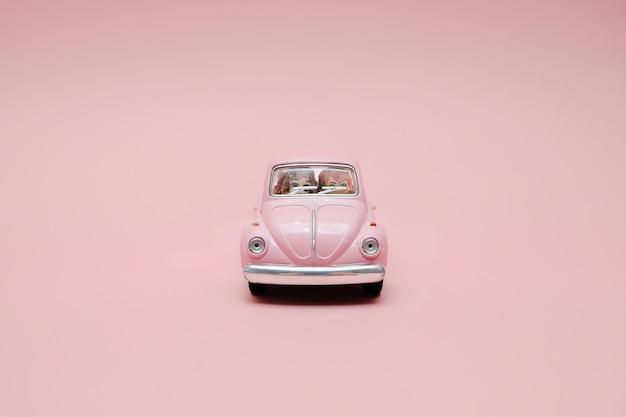 かわいいカップルとピンクのレトロなおもちゃの車