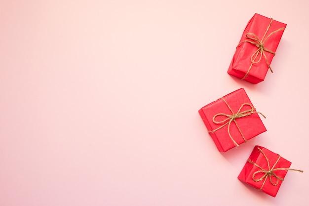 Красные подарочные коробки на розовом фоне.