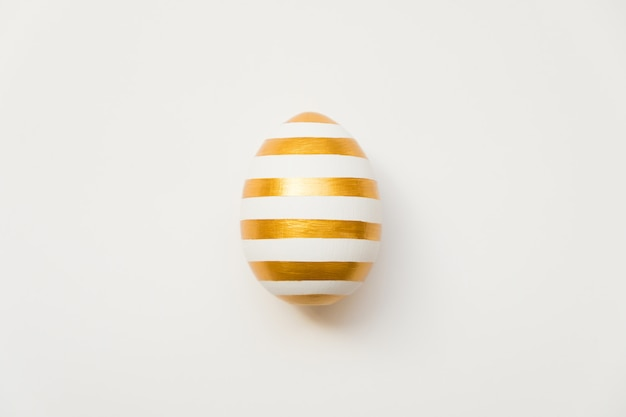 白い背景に分離された縞模様の黄金のイースターエッグ。ミニマルイースター