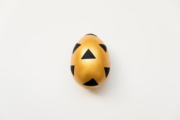 白い背景上に分離されて三角形の黒いパターンを持つ黄金のイースターエッグ
