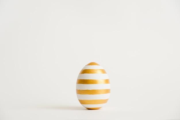 白い背景で隔離のストライプパターンと黄金のイースターエッグ