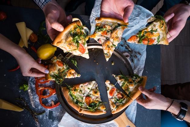 ピザを食べている友人。ピザのスライスをつかむ人の手