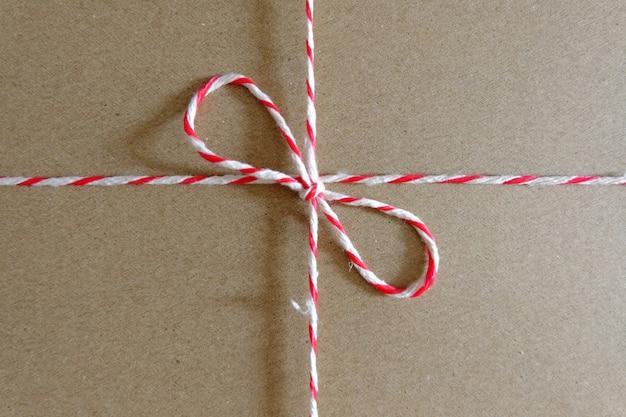 Красная и белая посылка веревка крупным планом на упаковке
