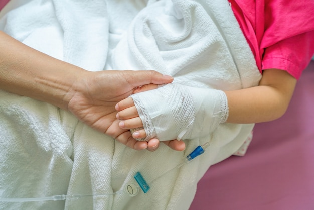 病院で点滴薬を服用している少年の生理食塩水を手に持つ母親