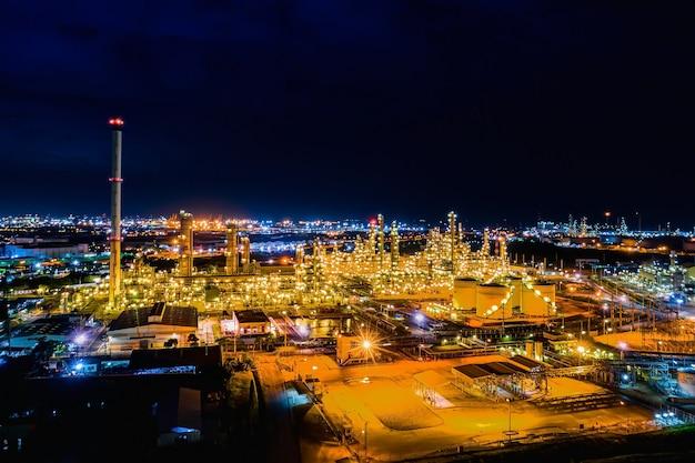 空撮。夕暮れと夜の石油精製工場と石油貯蔵タンク