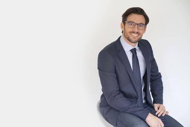 眼鏡をかけているスーツに座っている孤立した魅力的なビジネスマン