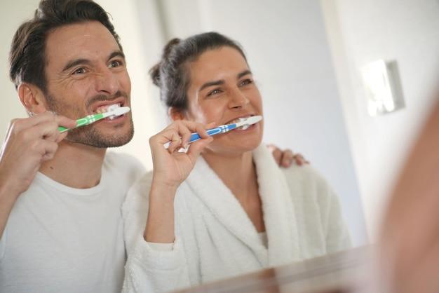 一緒に歯を磨く楽しい魅力的なカップル