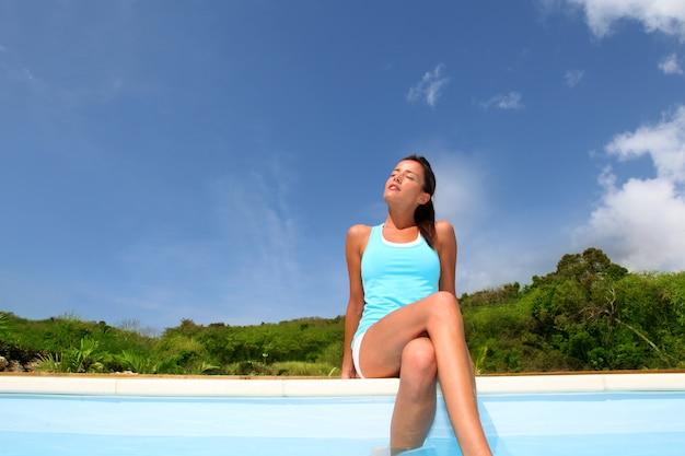 プールサイドでリラックスできるフィットネス服装のブルネットの少女