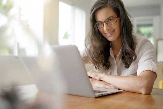 Красивая темноволосая женщина в очках работает на ноутбуке