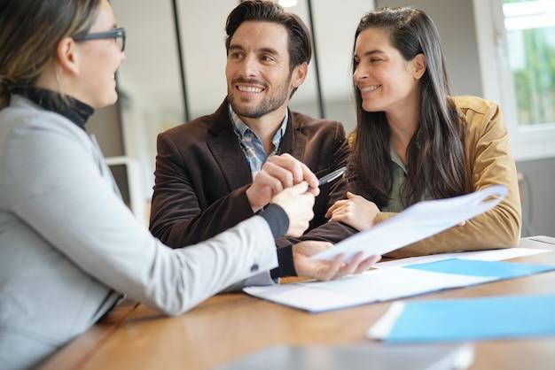 Привлекательная пара подписывает договор купли-продажи с агентом по недвижимости