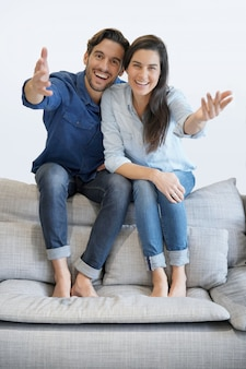 快適なソファの上のデニムで孤立した豪華な笑顔のカップル